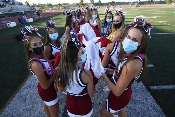 Herriman cheerleaders carry the American flag before the start of a high school football game against Davis, on Thursday, Aug. 13, 2020, in Herriman, Utah. Utah is among the states going forward with high school football this fall despite concerns about t