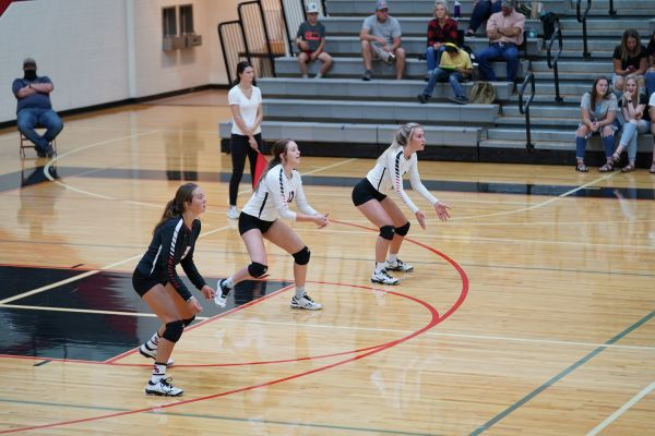 Ella Johnson, Kylee Wolter and Brinley Pickett await the St. Thomas More serve.