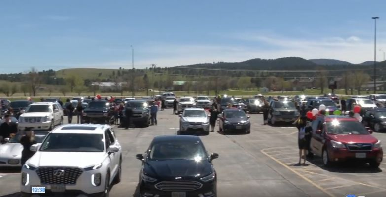 Students stand outside their vehicles as graduation begins Sunday in Sturgis.