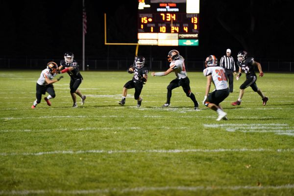 Scooper senior fullback Wren Jacobs blasts through the Huron defensive line for a 14-yard gain Friday night at Woodle Field.