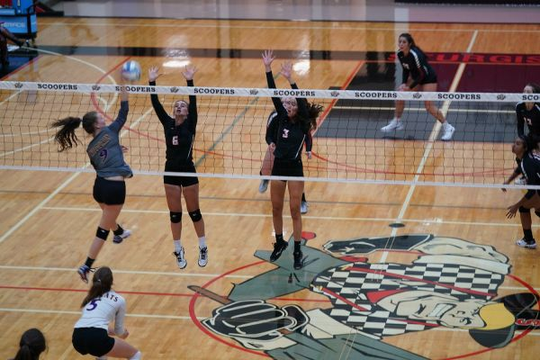Brinley Pickett and Jillian Beck attempt to block a kill by Custer middle hitter Heidi Moore.