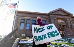 Jenae Ruesink holds a sign demanding a mask mandate from city council on Monday, Nov. 16, 2020 outside Carnegie Town Hall in Sioux Falls, S.D.