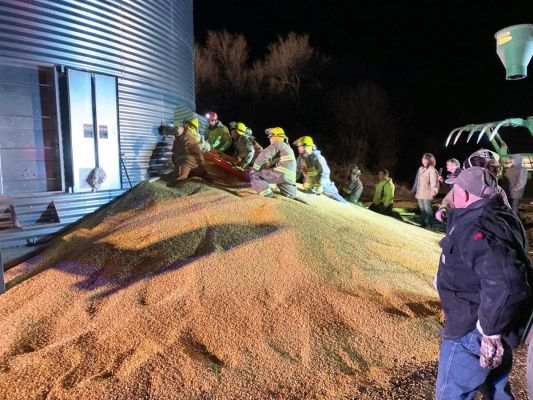 Dozens of neighbors and volunteers responded when a farmer became trapped in a 20,000 bushel grain bin, three--quarters filled with corn.