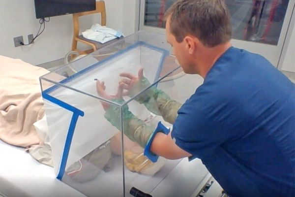 Brian Williamson, RN, BSN, Manager of Emergency Services at Monument Health Spearfish Hospital uses the airborne isolation shield created by Black Hills State University in a training video.